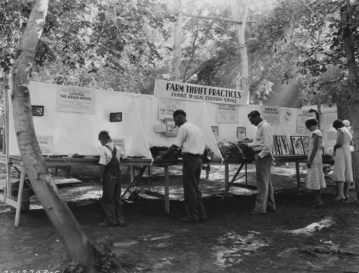 Men looking at the Farm Thrift Practice exhibit by the U.S.A.C Extension Service