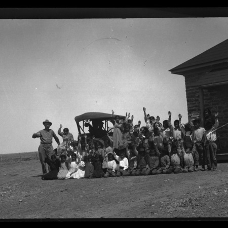 Tuba City Indian School poses, arms raised, in front of Maxwell automobile