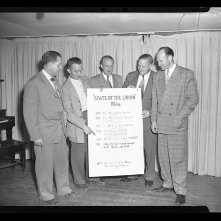"A Group of men with a ""State of the Union Building"" sign inside the Temporary Union Building, c. 1951"